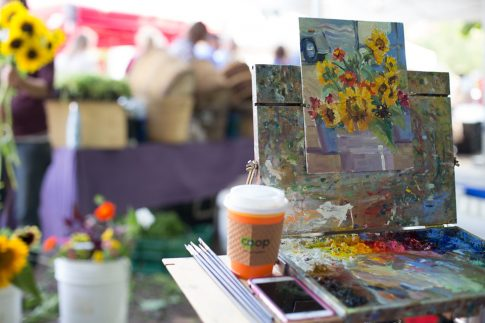 Plein air painting in progress on easel at downtown Traverse City farmers market